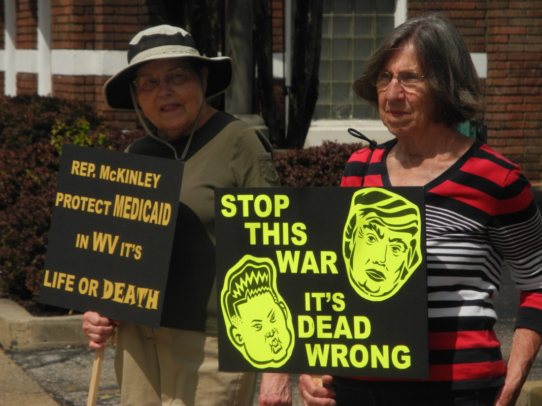 Photo by Ian Hicks Barbara Jenks of Valley Grove, left, and Carole Ryder of Wheeling hold signs across the street from the Federal Building in Wheeling Thursday, where a small group met with U.S. Rep. David McKinley, R-W.Va., to discuss concerns.