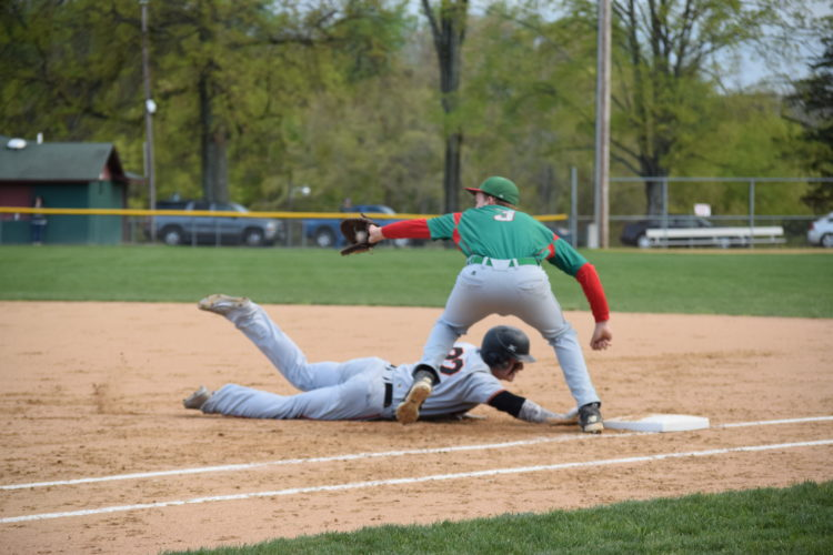 Linsly's Gage Giovengo dives back to first base ahead of the tag by  Barnesville's Aaron Marovich during the first inning    Photo by Rick Thorp