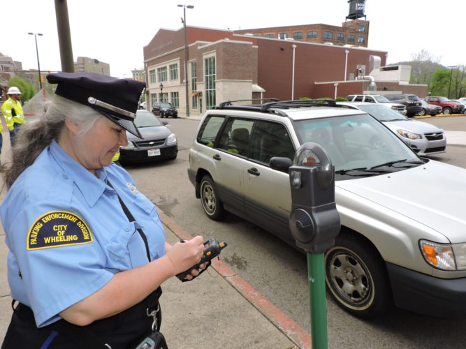 Photo by Casey Junkins Wheeling parking meter attendant Patricia Miller writes a ticket for an overtime citation along Market Street. On Tuesday, city council voted to increase the fine from $3 to $10, effective July 1.
