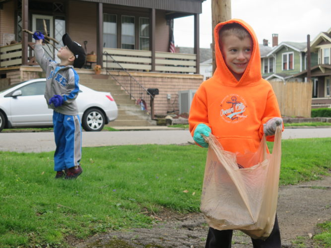 Photo by Alec Berry Dylan Coleman grips a plastic bag as he breaks from collecting litter, Saturday on Wheeling Island.