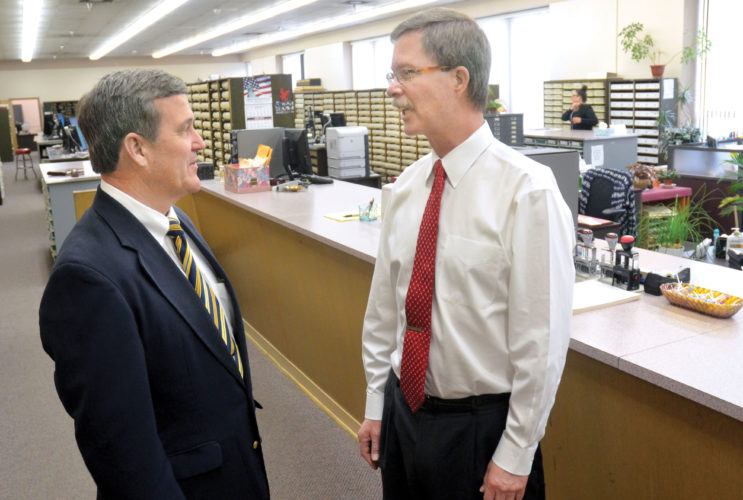 Photo by Scott McCloskey West Virginia Secretary of State Mac Warner, left, visits Monday with Ohio County Clerk Mike Kelly in Wheeling.