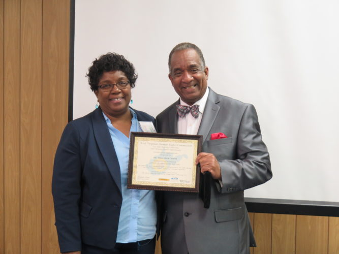 Photo by Joselyn King Yodora A. Booth, left, director of operations for the West Virginia Human Rights Commission, presents a certificate of appreciation to William White, executive director of the West Virginia Herbert Henderson Office of Minority Affairs, during the 2017 West Virginia Fair Housing Conference Tuesday in Wheeling.