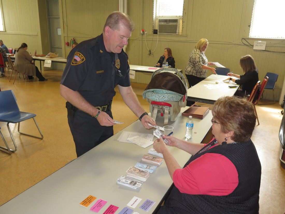 "Photo by Betsy Bethel Wheeling Police Chief Shawn Schwertfeger makes a stop at the ""bank"" during a program at the YWCA Wheeling Tuesday."
