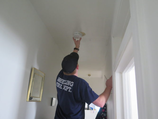 Photo by Alec Berry  Wheeling firefighter Nick Brown installs a smoke detector in a Wheeling Island home.