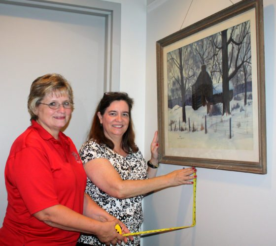 Wendy Morgan, director of alumni support and engagement, left, and Karen Wilmoth, director of development, hang a winter scene painting by the late Jesse Reed, former professor of art at D&E. Reed gave the painting to Elaine Dittmar, a former associate professor of chemistry, in the early 1970s. When Dittmar passed away earlier this year, the artwork was given to the College.