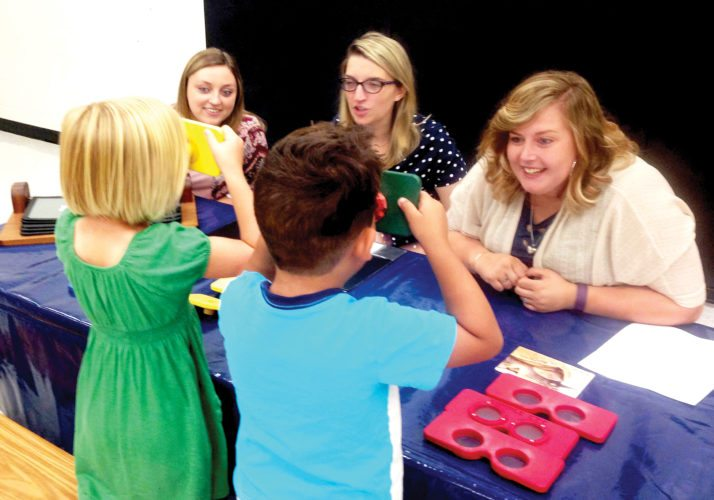 Davis & Elkins College education majors, from left behind table, Samantha Hornish, Katie Harris Shiflett and Katie Stalnaker lead Third Ward Elementary School students through an interactive station that allowed the youths to look through the eyes of an animal. Students learned that since owls don't have muscles behind their eyes, they have to move their heads to see what's next to them. Other lenses included a fly, mole and horse. The traveling program was presented by the Center of Science and Industry located in Columbus, Ohio.