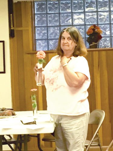 Vivian Shomo explains to members of the Emma Scott Garden Club the requirements of flowers during the group's September meeting.
