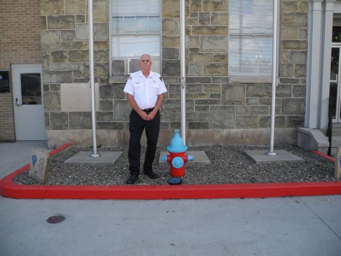 Elkins Fire Chief Tom Meader stands next to a newly painted fire hydrant. All the hydrants in the city are being flow-tested. After that, they will be painted with a particular color scheme to provide a visual indication of how much water the hydrant can produce per minute. (The Inter-Mountain photo by Brooke Binns)