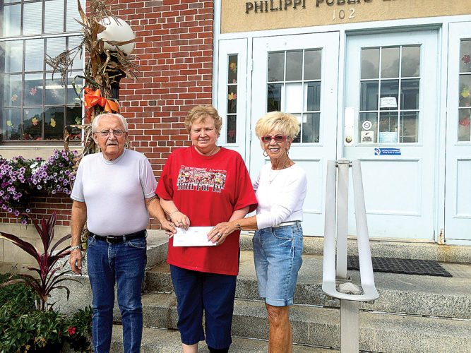 Philippi Public Library Librarian Judy Buckner Larry, center, received a donation from WFW Inc. for $500 as a donation toward the roof and heating and cooling system from Fred, left, and Donna Wilson.