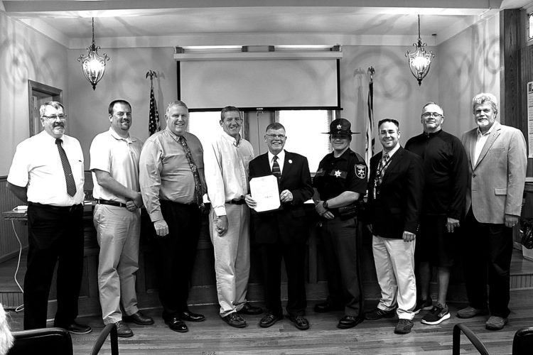The Barbour County Commission accepted a $20,000 PRO grant from Lynn Phillips, regional representative to Gov. Earl Ray Tomblin's office, at Thursday's meeting. The grant establishes Officer J. D. Roy as the Prevention Resource Officer at Philip Barbour High School. Standing from left are Commissioner Timothy McDaniel, Commission President Jedd Schola, Superintendent of Barbour County Schools Jeff Woofter, Commissioner Philip Hart, Phillips, Roy, Philip Barbour High School Principal Ron Keener, Delegate Danny Wagner and Doug Schiefelbein of Barbour County Schools.