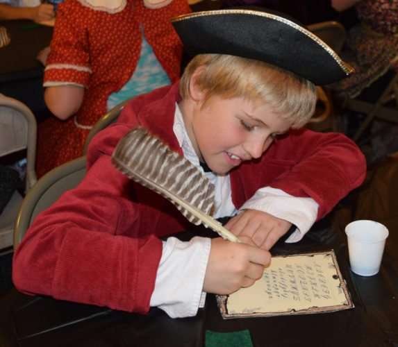 Brennen Smart uses a quill and ink to write his name on a hornbook Friday at the Beverly Heritage Center. Students from Beverly Elementary took part in a Colonial Day, where they had a taste of what schoolchildren studied, played, ate and dressed like in a former century.