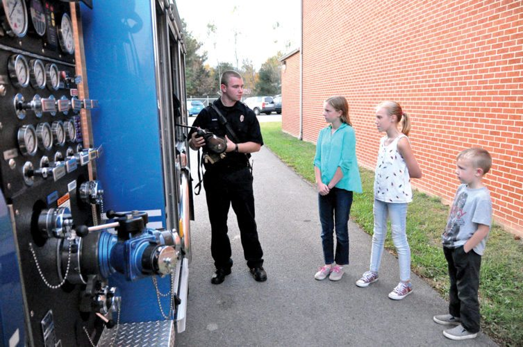 Firefighter Tyler Harris shows off one of the Elkins Fire Department's engine trucks to, from left, Natalie Sutton, Sophia Gillispie and Alexander Gillispie.