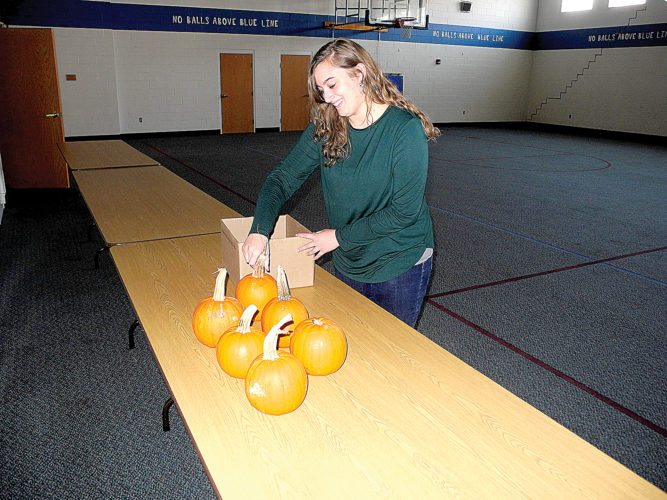 Newly named First United Methodist Church Director of Christian Education Kary Kramer sets up pumpkins as she prepares for this Sunday's 'All Saint's Day' party.