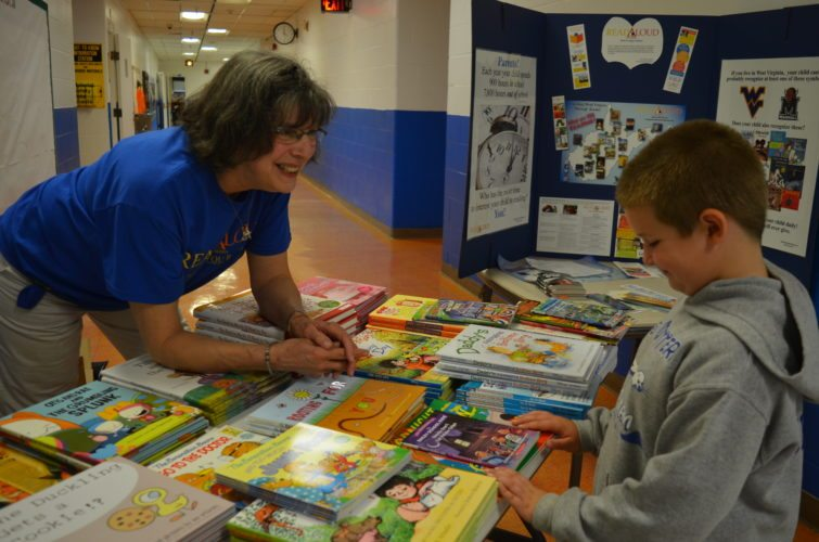 The Inter-Mountain photo by Beth Christian Broschart Read Aloud Randolph County Board Member Kay Young sets up at Jennings Randolph Elementary School Wednesday evening to distribute books to students before a PTO meeting. Young said this is the first time for giving books, and said a second distribution is slated for 9 a.m. at Coalton Elementary School Nov. 10 during the school's Veterans Day Program. Pictured, Young, on left helps JRES first-grade student  Jackson Sheperd select a book.