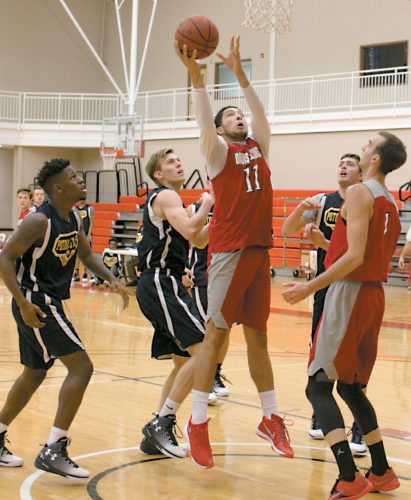 The Inter-Mountain photos by Kevin Hostetler The Davis & Elkins  College men's basketball team hosted a scrimmage game with  Potomac State Wednesday evening.  D&E forward Vladimir Milosevic battles for the ball under the basket.