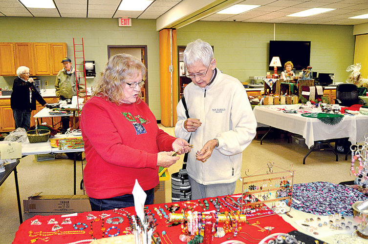 Many goodies are displayed at the Randolph County Senior Center Bazaar, including jewelry made by Sharon Zirkle, left, who shows her hand-made work to Dee Clark on Friday afternoon.