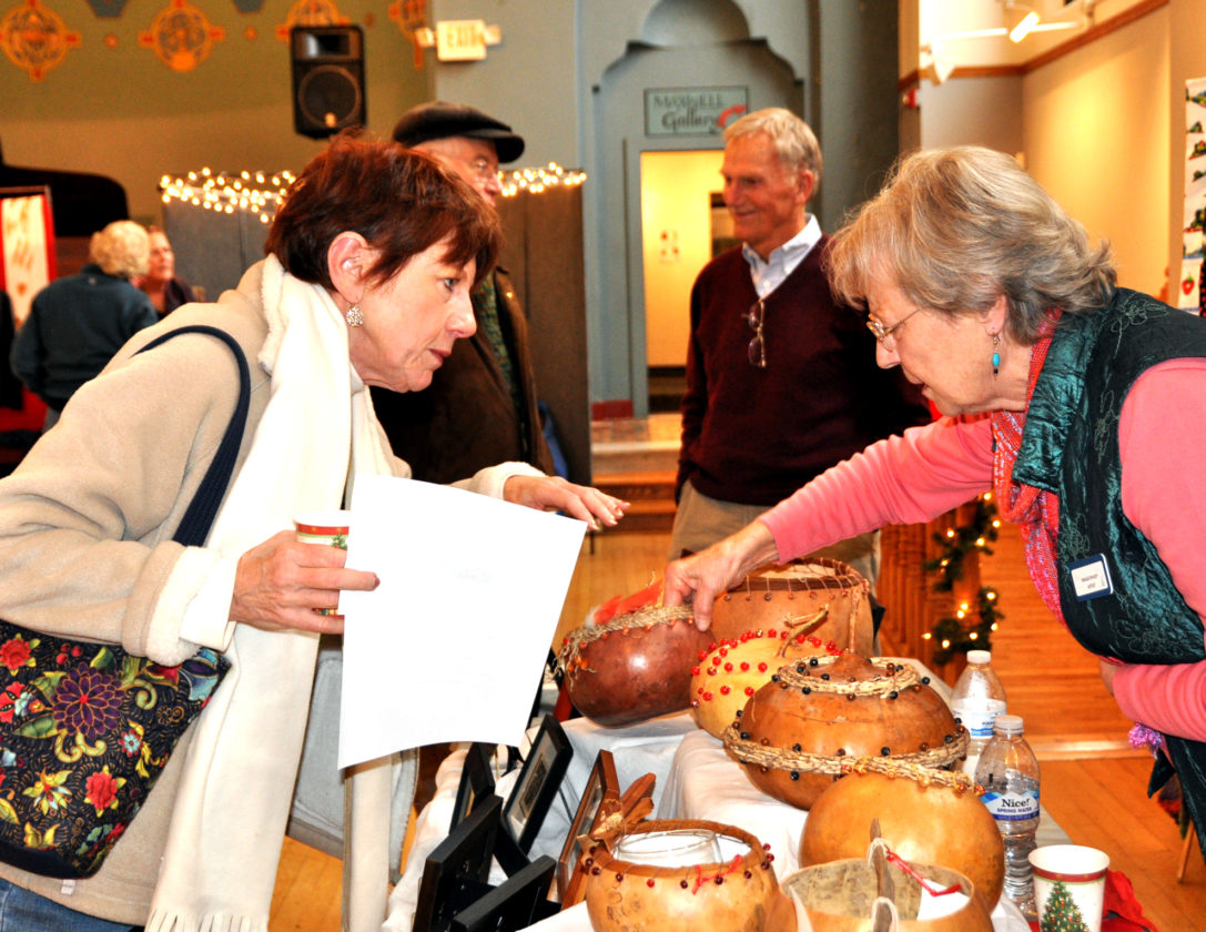 The Inter-Mountain photos by Tim MacVeanElkins resident Dottie Price, left, purchases a hand-crafted bowl from local artisan Maggi Rhudy, during the 2016 Holiday Artists Market hosted Friday and Saturday at The Arts Center