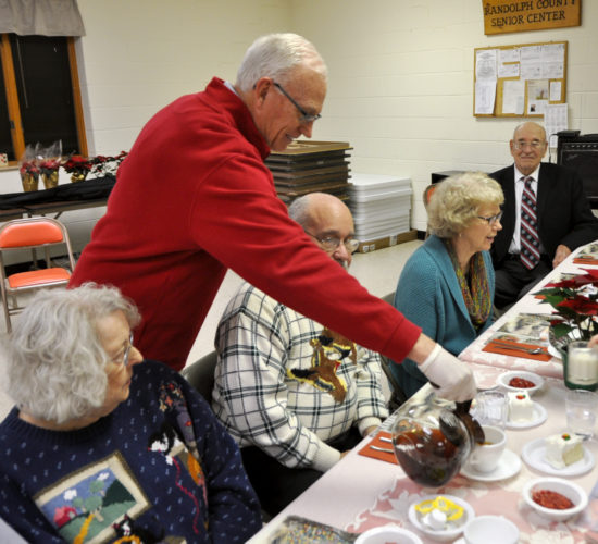 The Inter-Mountain photos by Tim MacVean Elkins Rotarian Mark Doak pours coffee for attendees of the 2016 Elkins-Randolph County Senior Center Christmas Dinner Friday night. Roughly 200 individuals attended the annual event. Elkins Rotary members served the meals, which consisted of roast beef, mashed potatoes and gravy, green bean casserole, cranberry salad, a roll and cake. The casserole and rolls were donated by Davis Medical Center. Volunteers from senior centers across Randolph County volunteered to help prepare and plate the meals