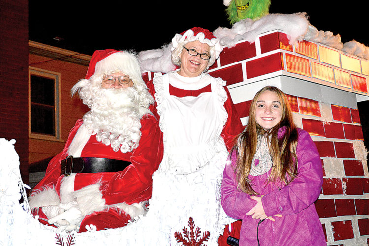 Santa and Mrs. Claus, along with Gracie Metheny, right, who provided music, wave to children that lined Davis Avenue for Wednesday night's Elkins Christmas Parade.
