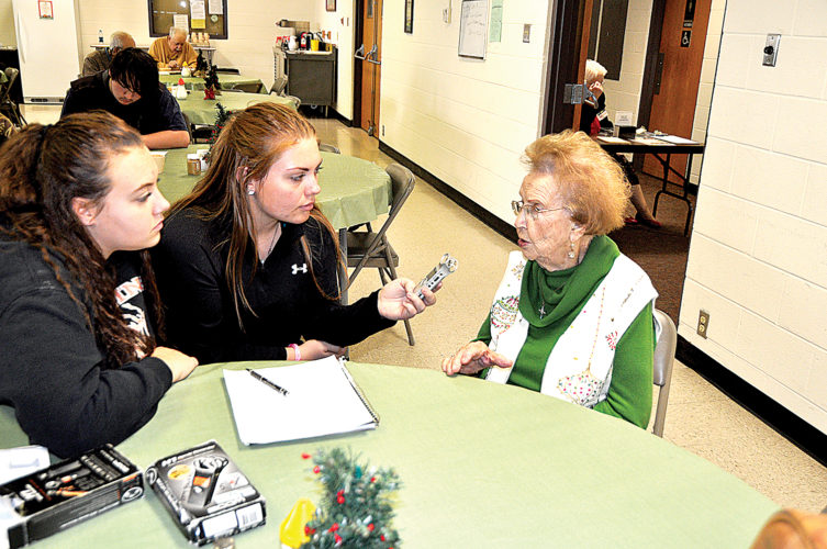 Elkins High School students Kelly Bennett, left, and Lexus Hicks, right, interview Ruth Hepler as part of an oral history portion of their folk music class on Thursday afternoon at the Randolph County Senior Center.