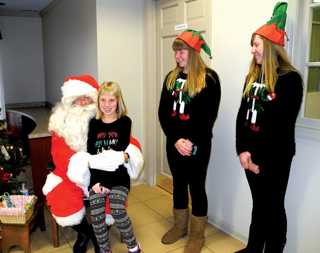 The Inter-Mountain photo by Tim MacVean Olivia Moudry, 11, of Elkins, tells Santa Claus she wants a new American Girl doll and doll clothing while paying him a visit at Davis Trust Company Friday afternoon. Also on hand are elves Heather and Haley Harris, handing out candy canes and coloring books.