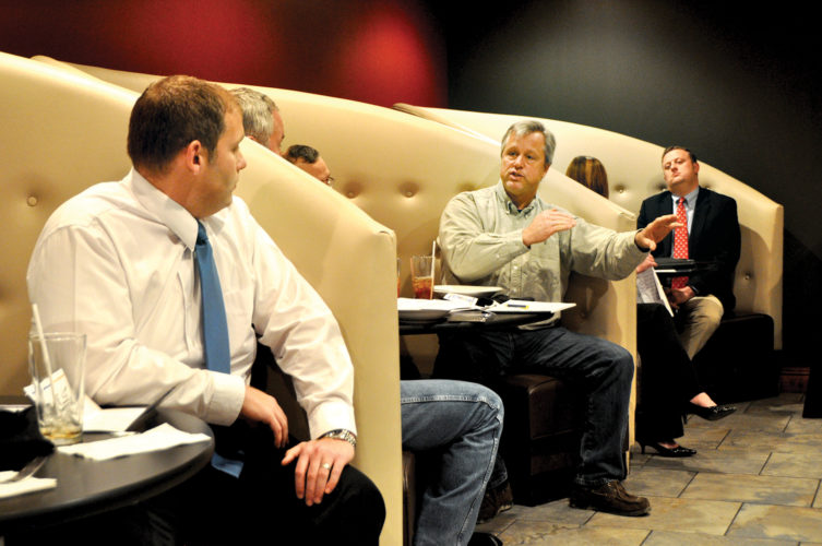 Randolph County Prosecuting Attorney Michael Parker, left, along with other elected officials, listen as Sen. Robert Karnes, R-Upshur, third from right, offers an opinion Thursday during a County Commissioners' Association of West Virginia regional meeting at Vintage Restaurant and Wine Bar in Elkins.
