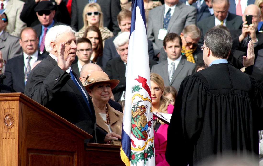About to become West Virginia's 36th governor, Jim Justice takes the oath of office from Tucker County native Chief Justice Allen H. Loughry II Monday during the inaugural ceremony at the state Capitol in Charleston. Justice's wife, Cathy, holds the Bible as Justice takes the oath.