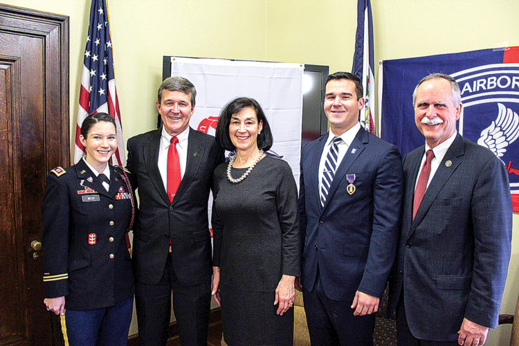 Retired U.S. Army Capt. Steven Warner, second from right, receives the Purple Heart during a ceremony Monday in Charleston. With him, from left, are his sister, U.S. Army Capt. Lisa Warner Miller; his father, West Virginia Secretary of State Mac Warner; his mother, Debbie Warner; and U.S. Rep David McKinley, R-W.Va.