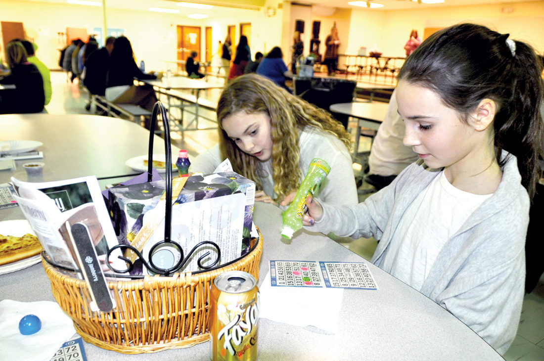Sixth-graders Samantha Sproul, right, and Hannah Martin play bingo during Wednesday's Family Night event at Elkins Middle School, which offered games, pizza and the opportunity to learn more about an after-school program called Project ISAAC.