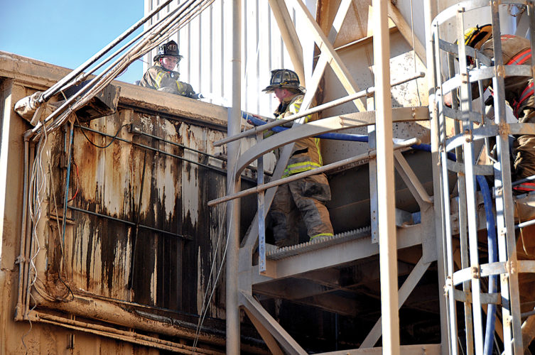 Firefighters with the Elkins Fire Department and Beverly Volunteer Fire Department run a hose to the top of a building on the campus of the Hamer Pellet Mill in South Elkins Friday morning after a bearing going bad in a pellet press started a fire in the duct work of the facility.