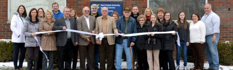 The Inter-Mountain photo by Katrina Duckworth Commission President Terry Cutright, Commissioner Troy 'Buddy' Brady and Commissioner Sam Nolte cut the ribbon commemorating the opening of their new office space in Buckhannon along with county staff and community members.