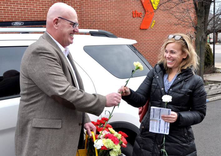 The Inter-Mountain photos by Tim MacVean In honor of 'Kindness Counts Week,' Elkins Mayor Van Broughton presents Sue Gillispie with a carnation Tuesday afternoon. Broughton walked through downtown handing out flowers in the afternoon.
