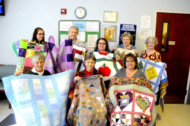 The Inter-Mountain photo by Beth Henry-Vance Members of the Log Cabin Quilters' Guild donate 10 quilts for dialysis patients Monday at Fresenius Kidney Care in Elkins, and they have at least 15 more that will be finished soon. Guild members work on supplying the center with quilts year-round, and they try to make sure every patient receives one. Linda Coleman, secretary at the dialysis center, said it means a lot to patients to receive such beautiful handmade gifts.