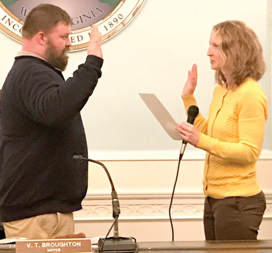 Elkins City Clerk Jessica Sutton, right, administers the oath of office to Christopher Lowther, who was appointed to City Council Thursday night.