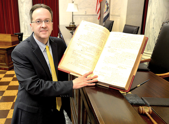 Chief Justice Allen H. Loughry II shows a book of handwritten court orders from the 1830 he discovered when he was first elected to the West Virginia Supreme Court of Appeals.