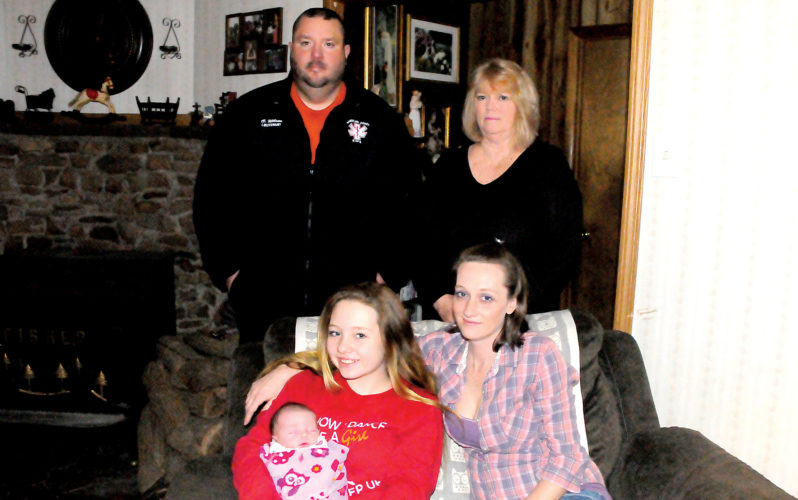 The Inter-Mountain photo by Beth Henry-Vance Newborn Rylee Annalice Cooper is held by her big sister, Maddie. Their mother, Trasonda 'Toodles' Noel, is seated at right, and in back are Chris Wilson, emergency medical technician lieutenant with the Randolph County Emergency Medical Services, and grandmother Suzanne Noel, who delivered the baby in a surprise home birth earlier this month