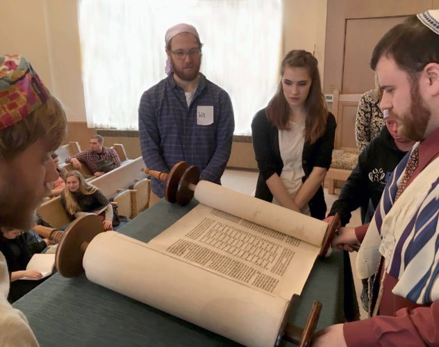 Submitted photo As part of the Peacemaking in Appalachia conference, students from Davis & Elkins College visit the Tree of Life Synagogue in Morgantown. Westminster College student Josh Mascoop, right, reads from the Torah Scroll and is observed by, from left, D&E students Jonathan Gabel, Will Roboski and Abbagayle Peterson and Westminster student Hunter Steinitz.
