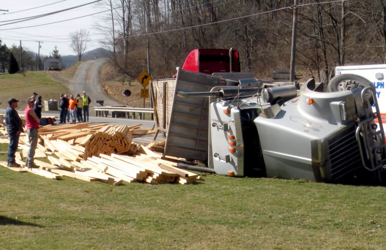 The Inter-Mountain photo by Lindsay Hawken A tractor-trailer, owned by Maple Leaf Trucking out of Slaty Fork, comes to a stop on its side after a tire on the vehicle blew out. The driver was transported to David Medical Center for observation, but suffered no serious injuries as a result of the crash.