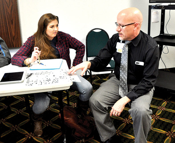Mike Bell goes over design ideas with a West Virginia University student as Elkins Main Street officials discuss possible plans for a modified traffic route to the Railroad Depot.