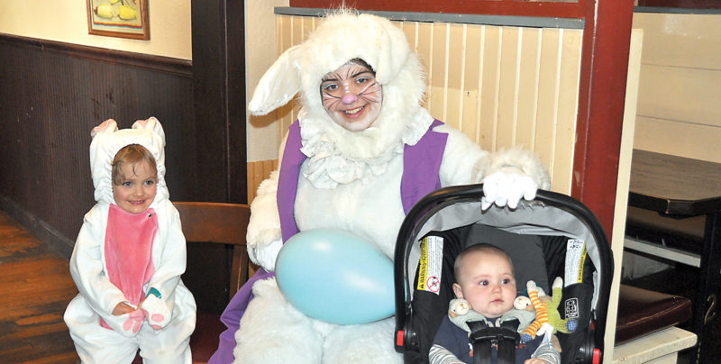 The Inter-Mountain photo by Tim MacVean Four-year-old Hallie Riddle, left, plays dress-up as she and her 6-month-old brother, Henry, enjoy pancakes with the Easter Bunny Saturday morning at C.J. Maggie's in Elkins. The annual event is put on by Elkins Main Street and numerous volunteers from the Old Brick Playhouse and community members who donate their time.