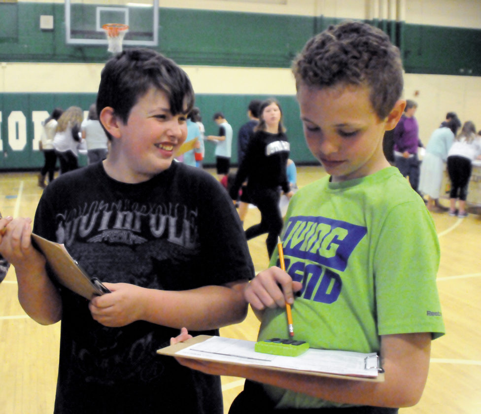 Elkins Middle School sixth-graders Josh Arbogast, left, and Zack Bonnell participate in a budget program Tuesday called 'Get A Life.' The program teaches students about how important budgeting and using money wisely will be to them as adults.