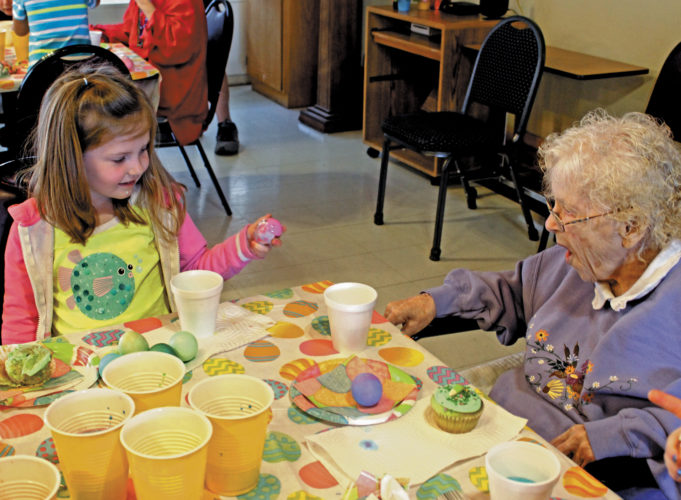 The Inter-Mountain photo by Brooke Binns Students from Shining Light Pre-School visited Nella's Inc. and Nella's Nursing Home on Tuesday to color Easter eggs with Nella's residents. Lily Perry, left, shares her finished egg with Nella's Inc. resident Kathleen Cain after a fun-filled afternoon shared together.