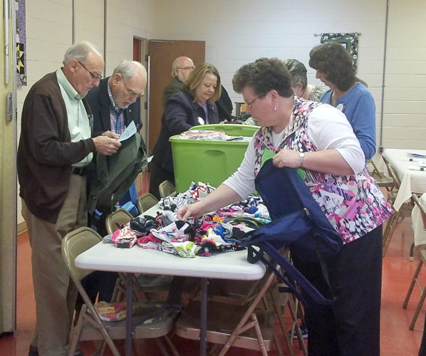 The Inter-Mountain photo by Kristi Groves Buckhannon Rotary Club members fill 96 backpacks with items for boys and girls ages 2 through 14 that have been placed in the foster care system. Items placed in the backpacks included toothpaste and a toothbrush, a comb/brush, a blanket, a stuffed animal/doll, a reading book, crayons, a coloring book/activity book, a pen, a pencil, a sharpener, a blank page tablet and tissue packets. This is the fourth year the Buckhannon Rotary Club has made the backpacks available for children entering into the foster care system