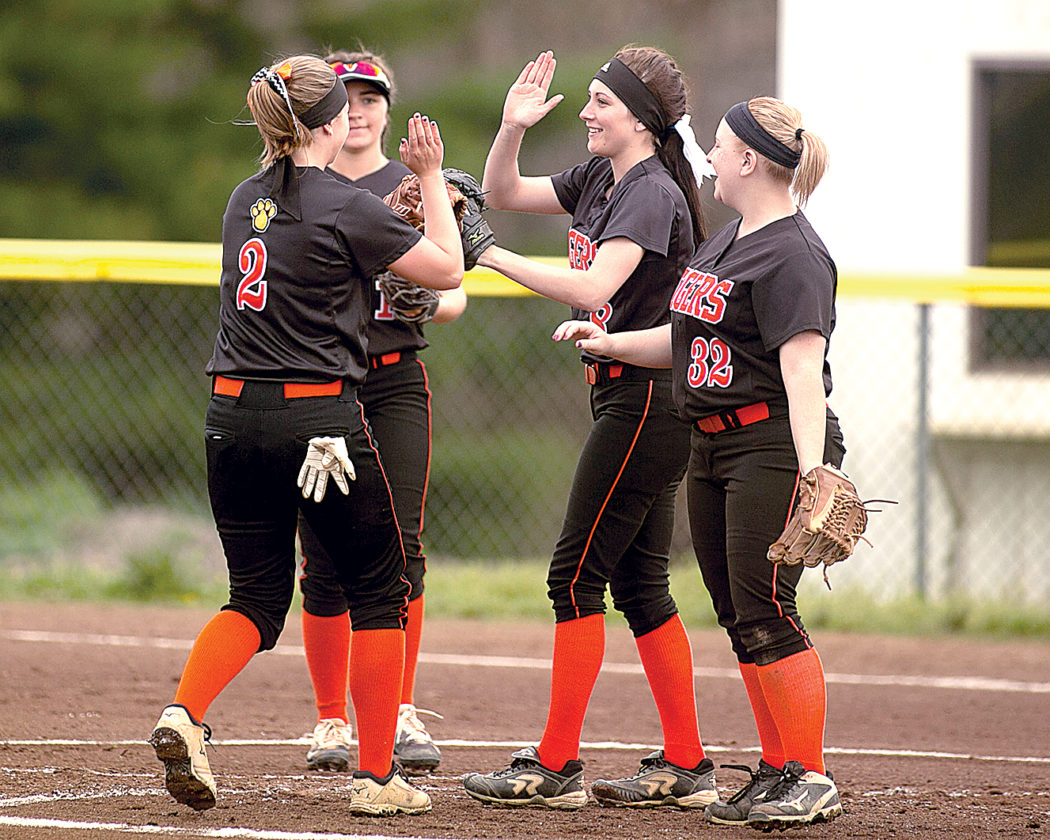 Elkins teammates Haley Collett, Korri Evans and Madison Wagner celebrate the Lady Tigers' win Thursday.