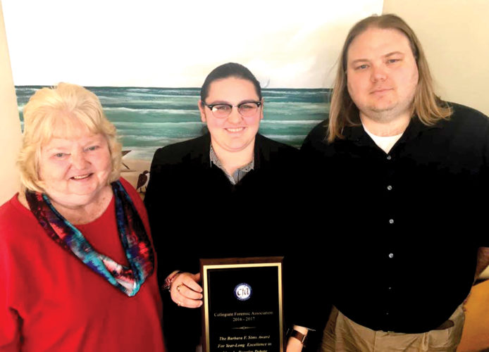 Davis & Elkins College senior Emily Coffman, center, is congratulated by Dr. Barbara Sims and Dr. Brent Saindon on receiving the Barbara F. Sims Award for Year-Long Excellence in Lincoln-Douglas Debate. The award was presented to Coffman for her excellence in debate for the 2016-2017 academic year.