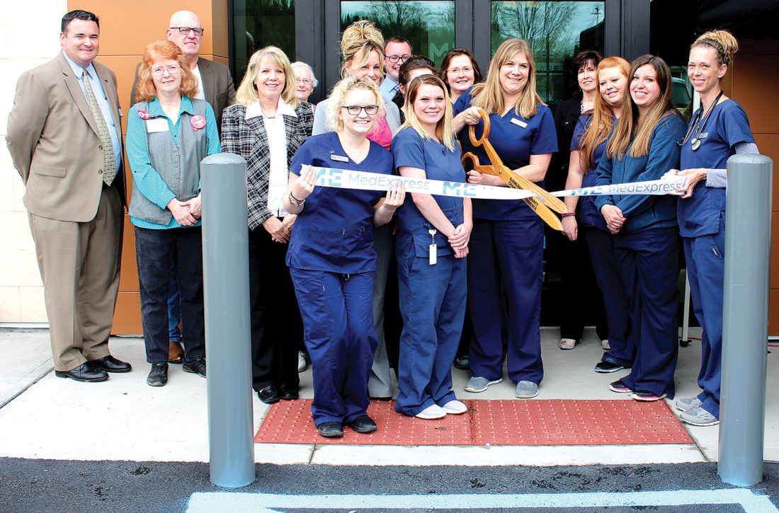 Center Manager Julie Simmons cuts a celebratory ribbon at the MedExpress open house in Elkins on Tuesday with representatives from the Elkins-Randolph County Chamber of Commerce and MedExpress officials.