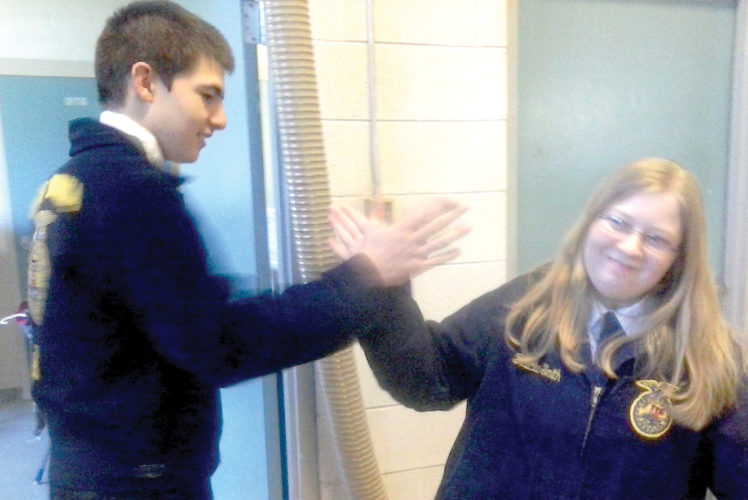 Logan Rowan, FFA sentinel and Sanya Zickefoose, vice-president, high-five each other after participating in the FFA Regional Competitions.