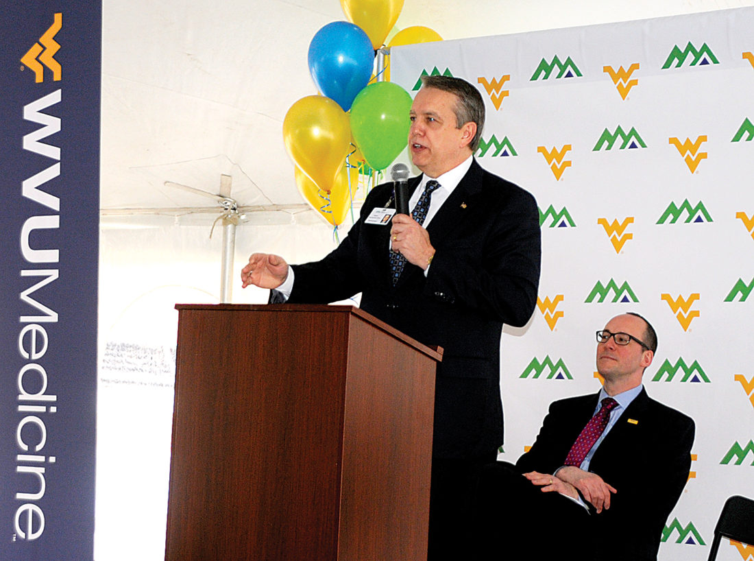 Davis Health System President and CEO Vance Jackson, center, speaks to a large crowd Wednesday morning celebrating the hospital's partnership with West Virginia University Medicine. Albert L. Wright Jr., right, president and CEO of WVU Health System, looks on.