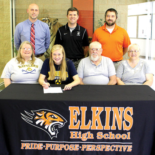 Brooke Pomp signs a letter of intent to play soccer for Alderson Broaddus University Thursday surrounded by supporters. From left are Brooke's mother Susan, Brooke, her grandfather Charles Reed and grandmother Vicki Reed; and, back row from left, Elkins High School Assistant Principal Amrit Rayfield, head women's soccer coach Scott Cutright and athletic director Adam Roth.