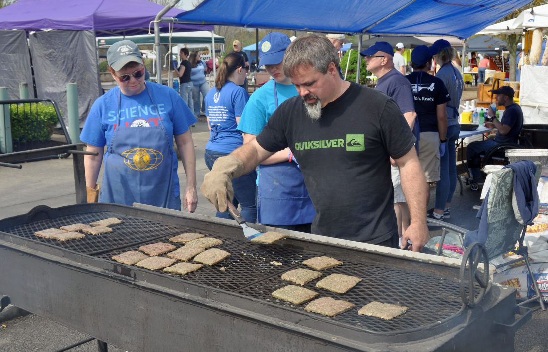 The Inter-Mountain photo by Tim MacVean Kiwanis International member, from left, Beth Adams, Tygart Valley Key Club member Joelle Whittemore and Kevin Tingler prepare ramp hamburgers at Saturday's Ramps & Rail Festival.